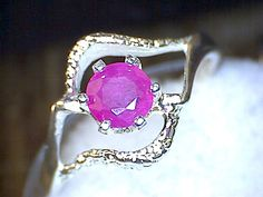 Neat 5+ mm 0.50+ carat round cut Afghan ruby swirl ring in sterling silver..Ring is a size 6..