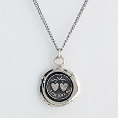 Pyrrha's Hearts Talisman Necklace.  This handcrafted wax seal necklace features two hearts tied with a ribbon symbolic of the uniting of two souls and reads Forever.