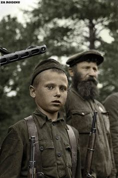 Russian partisans managed to choke German supplies and transportation. Here a  child stands with an older man, partisans if caught by the Germans were shot.