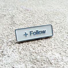"""This is undoubtedly one of all of our favourite buttons to click on our social media channels. Now follow your favourites in real life by rocking this classy soft enamel """"+ Follow"""" lapel pin and bring social media to life! Size 1.25"""" in width."""