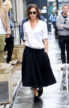 Victoria Beckham wears a white button down shirt with midi-skirt and black boots.