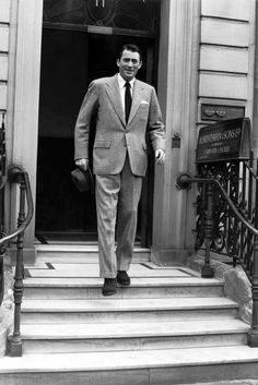 Gregory Peck stepping out of Savile Row tailors H. Huntsman, 1953; grey flannel suit, white point-collar shirt, dark brown chukka boots