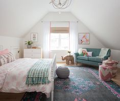 Charming girls bedroom boasts a white Jenny Lind Bed dressed in pink elephant bedding accented with a gray and green fringe throw blanket and placed on a blue and pink rug behind a gray knitted pouf.