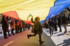 A child runs under a large flag as supporters of the monarchy march to celebrate the 94th birthday of former Romanian King Michael I, in Bucharest, Romania, Sunday, Oct. 25, 2015. Monarchy supporters carried a 150 meters long flag on a main boulevard in the Romanian capital to celebrate the former king's birthday. (AP Photo/Vadim Ghirda)