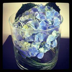 Blauwe hortensia met gras in grote vaas (of vissenkom).