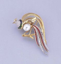 A DIAMOND, PEARL AND GEM-SET BIRD BROOCH  Designed as a bird of paradise, the pearl body with pavé-set diamond head and gem-set collar to the baguette-cut diamond and ruby plumes, circa 1960, 7.7 cm. high