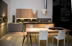 Wood kitchen cabinets, decorative wall panels and large dining table made of natural wood, one of simple and functional modern kitchen trends in 2013