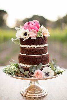Brides.com: . A two-tiered chocolate naked cake filled with vanilla buttercream and topped with fresh peonies, ranunculus, and roses, created by Deux Bakery.