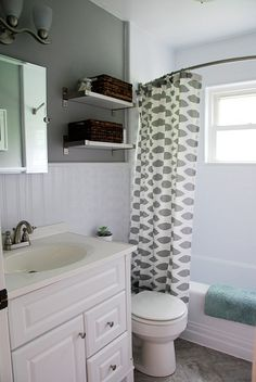 Inspiring bath remodel, including wainscot, a new bath tub surround, and peel n' stick tiles over old tile with real grout. Nice! Though I would do WOOD wainscot, and not that plastic stuff.