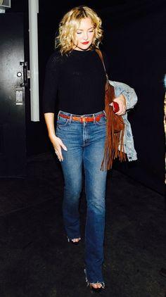 Kate Hudson wears a turtleneck, flared jeans, braided belt, fringe shoulder bag, and sandals