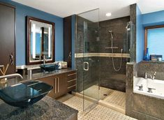 Constructed for two people, this inviting master suite with its deep color palettethink chocolate-brown cabinets and an evening shade of blue for the walls features his-and-her vanity spaces, a custom shower and whirlpool tub.