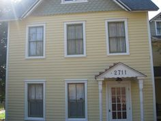 yellow farmhouse green metal roof - farmhouse windows, black with white trim