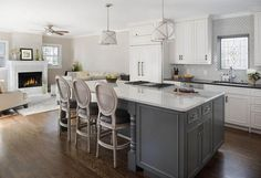 White and gray kitchen features white perimeter cabinets paired with black quartz countertops and a marble diamond pattern backsplash.