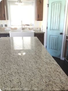 love this countertop called Giallo Ornamental, has the grey/black/browns in it, would look great in a white kitchen... House of Smiths
