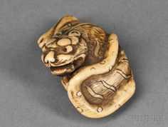 Ivory Netsuke of a Tiger, Japan, 18th century, reclined with its head turned toward the rear, with inlaid eyes, unsigned, ht. 1 1/4, wd. 2 1/4 in.