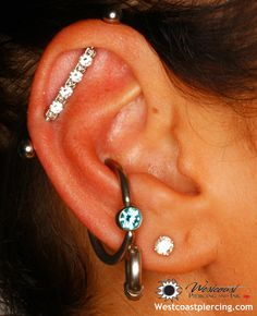 Beautiful Channel Set jewelled Industrial barbell from  Industrial Strength dresses up this ear. Conch has a 12ga CBR with a Mint Green CZ from Anatometal.