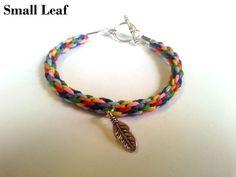 A handmade toggle bracelet made with a kumihimo braid of rainbow colours, and a choice of charm.