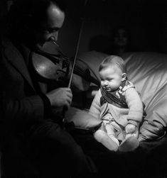 Django Reinhardt plays the violin to his son Babik © 1945 Émile Savitry