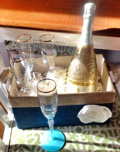 Beautiful handmade engagement gift for under $35! A set of four gold rimmed champagne glasses from a thrift store,  painted glass bottoms made with handmade teal chalk paint (paint and unsanded grout), gold glitter decoupaged on a champagne bottle and then sprayed with spray-on glue, and completed with a box of chalk and a teal and gold basket!