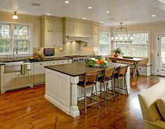 Amazing kitchen with apron sink and neutral cabinets, all grounded by the large plank flooring