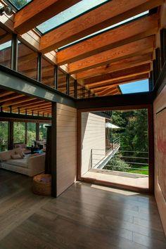 de hal in het midden van het huis heeft een glazen dak waardoor het hele huis heel licht is. Mooi de duidelijk zichtbare constructie