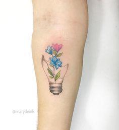 Tatuagem criada por Mary Ellen de João Pessoa. Flores coloridas e delicadas saindo de lâmpada quebrada.