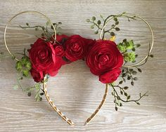 These floral wire Minnie ears are inspired by Beauty and the Beast. Sitting atop the headband are red ranunculus, climbing vines, Lumiere and Cogsworth or Belle and Beast! You have the option of a plain black satin covered headband, or one done with a woven grosgrain ribbon in gold and cream.