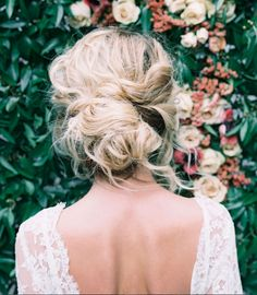 Real Inspiration for the Perfect Wedding Updo | Created by pulling loosely curled hair into a messy bun, this easy-breezy updo was instantly one of our favorites! It's perfect for a boho or beachy wedding and pairs perfectly with earth-toned eyes and pink cheeks.