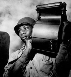 US Navy Miles Davis King carrying a loaded magazine for a 20-mm gun aboard CVE USS Tulagi en route to France August 1944.