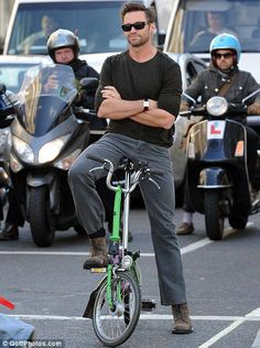 Hugh Jackman on a Brompton folding bike. Note that the scooterists have actually BACKED away from Wolverine, stopping only when they touched the buses behind them!