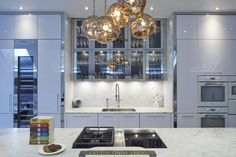 A cluster of Tom Dixon 'Melt' pendant lights in copper above the kitchen island in a London home.