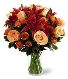 Captivating Autumn Bouquet Peach roses mingle with rusted Asiatic lilies, orange mini roses and greenery gorgeously arranged in a clear glass vase.