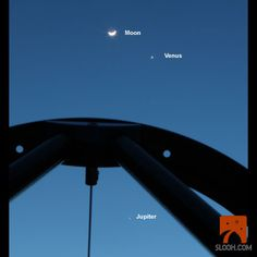 Here is a snap from the Slooh conjunction event - unique angle looking up through the telescope truss tube with the Moon, Venus, and Jupiter all in the same field of view.