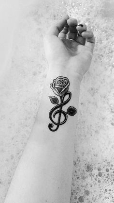 my treble clef tattoo & a rose growing out of it.