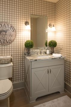 Glamour meets a hint of country in this cream powder room. The granite counter tops and neutral color palette give elegance to the space while the gingham wallpaper and wall art offer a splash of country.