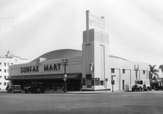 1933)* - Exterior view of the Sunfax Mart, a food market, located on the corner of Sunset Boulevard and Fairfax Avenue, hence the name Sunfax. The market includes a Van de Kamp's Bakery on the corner, where the miniature windwill is seen mounted on the building.