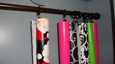 curtain rod with pinch drapery hooks to hold wrapping paper and keep it tidy.