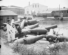 A group of British sailors posing with old guns at a Turkish dockyard in occupied Istanbul, WWI