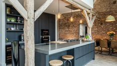 Het kookeiland past precies tussen de originele houten spantenstructuur. De houten balken geven extra sfeer in de keuken. Het uitstekende deel van het volume met de studie leunt ook echt op de houten horizontale spantbenen.