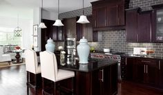 modern traditional | gray subway tile + dark wood cabinets + cabinet uppers of various heights + cabinet hardware