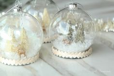 To make these DIY snow globe ornaments, snatch up a bunch of clear plastic ornaments from your local craft store, then fill them with animal figures, mini trees, and faux snow.