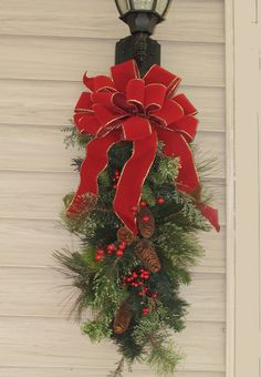 Features: -Great decoration for front door or outside lamp post. -Handcrafted bow made with red velvet wired Christmas ribbon. -Lush pine swag with pinecones and berries. -Product may ship compres