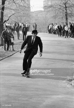 Watched by onlookers, a man in a suit and sunglasses rides a skateboard down a hill path in Central Park, New York, New York, 1965.