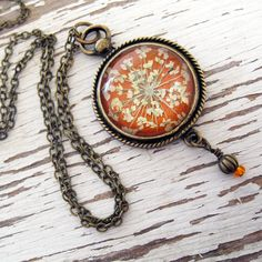 pendant made from real pressed queen anne's lace flower petals in antique brass setting. by Denver's Winter Garden Studios
