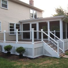 A Fiberon deck and railing with a gable style screened porch and lighting in the back yard. A portico and flagstone walkway in the front.