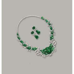 JADEITE AND DIAMOND NECKLACE AND PAIR OF MATCHING PENDENT EARRINGS. The necklace composed of floral motifs, set with numerous carved jadeite plaques of translucent rich emerald green colour, decorated with brilliant-cut diamonds, length approximately 390mm, detachable brooch fitting; and pair of matching pendent earrings; the diamonds altogether weighing approximately 5.60 carats, mounted in 18 karat white gold.