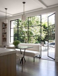 Love the sleek lines of the glass doors in this chic breakfast room that opens out to the patio from Roses & Rust.