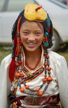 https://flic.kr/p/tHhFuR | She is wearing her family`s jewelry, Tibet 2014 | Tibetan girl at the horse race festival, on the vast peltang plain near Yushu. She wears her family's treasured jewelry. She wears an turquoise, coral and amber headdress, and neckles with coral and Zi stone (Kind of onyx with zebra-like banded designs, two eyes--regular, three eyes--good, 9 eyes--best).