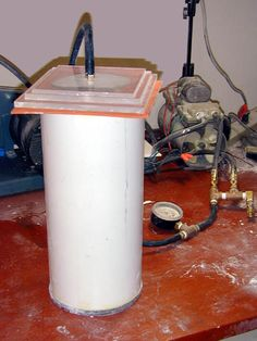 DIY vacuum chamber (a concrete cylinder with a couple of layers of glass for a window covering the top. Could also be used as a high-pressure chamber, if weight is added to the glass window.