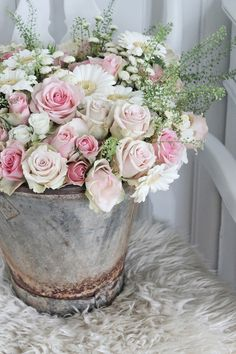 Pretty for rustic/shabby wedding: Roses and daisies in rustic metal bucket.